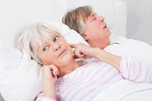 Woman awake in bed covering her ears because of husband's sleep apnea near Beachwood, OH